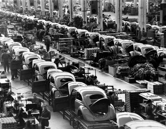 FILE - In this June 16, 1954 file photo, VW beetles are assembled in lines at the Volkwagen auto works plant, which manufactures nearly 900 automobiles each day, in Wolfsburg, West Germany. Thanks to Volkswagen, Wolfsburg boomed in West Germany's postwar rebirth and today the town and the company are inseparable. Volkswagen is halting production of the last version of its Beetle model in July 2019 at its plant in Puebla, Mexico, the end of the road for a vehicle that has symbolized many things over a history spanning eight decades since 1938.(AP Photo/Albert Riethausen, File)