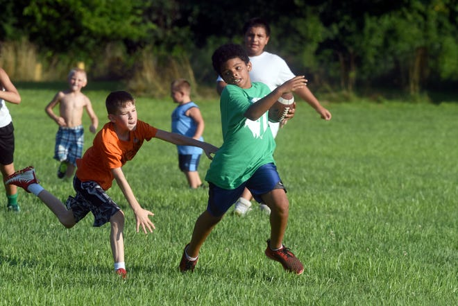 """Quantez """"Dada"""" Pletcher runs with the ball during a recently two-hand touch scrimmage for the East Tigers at Armco Park. The league has been providing football for more than 60 years."""