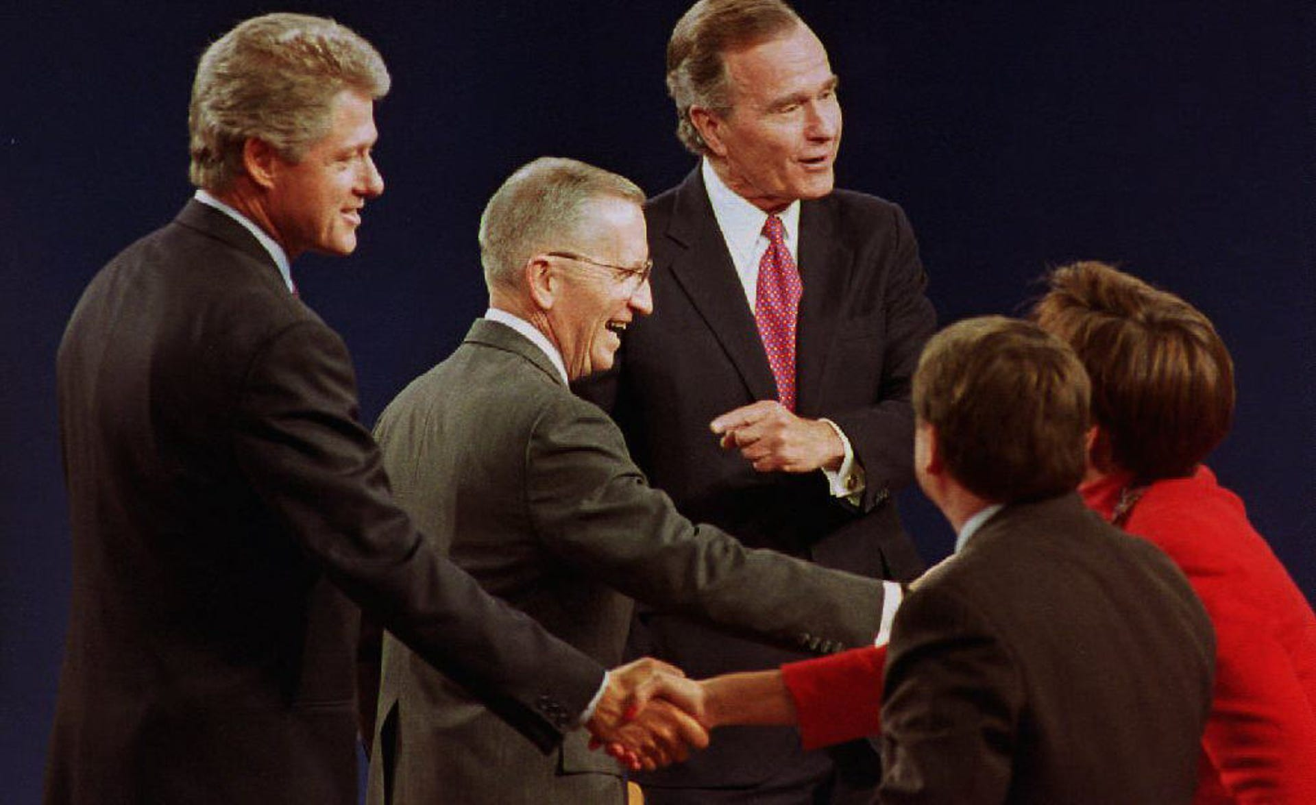 Former US presidential candidates Bill Clinton (L), Ross Perot (C) and President George Bush (R) shake hands with the panelists after the conclusion of their final debate in East Lansing, Mich. on Oct. 19, 1992