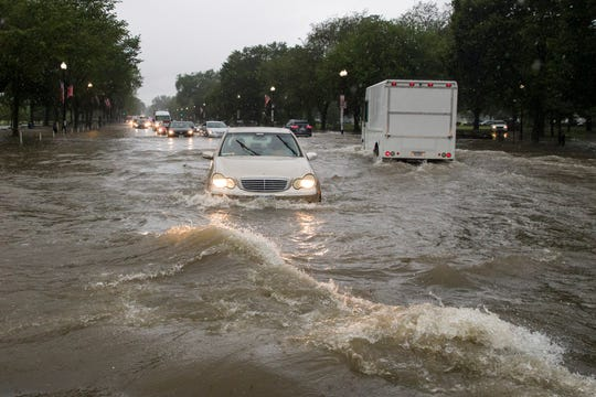 Heavy rain storms flooded an intersection in Washington, D.C. on Monday July 8, 2019, stalling cars in the street.