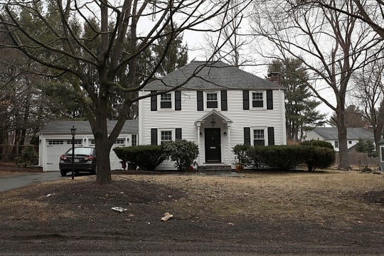 In this March 20, 2019 file photo a home that once belonged to Peter Brand sits among trees, in Needham, Mass. Harvard University has fired Brand, its longtime fencing coach, over the sale of his suburban Boston home to a wealthy businessman whose teenage son was later admitted to the school and joined the team.