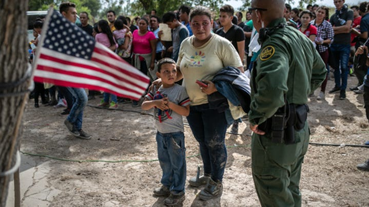 A U.S. Border Patrol agent speaks to immigrants after taking them into custody on July 02, 2019, in Los Ebanos, Texas. Hundreds of immigrants, most from Central America, turned themselves in to border agents after rafting across the Rio Grande from Mexico to seek asylum in the United States.