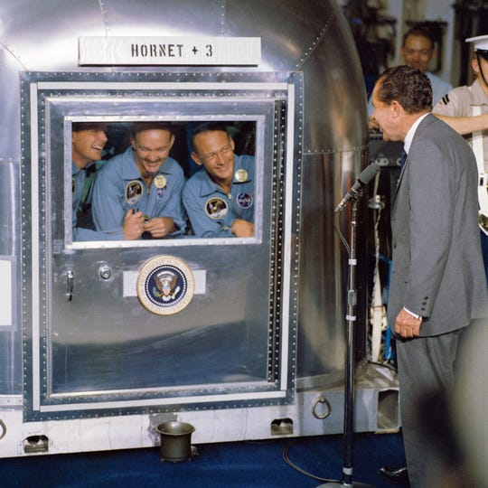 President Richard M. Nixon welcomes the 'Apollo 11' astronauts, Neil Armstrong, Michael Collins and Edwin Aldrin confined in the Mobile Quarantine Facility aboard the 'USS Hornet',  July 24, 1969.