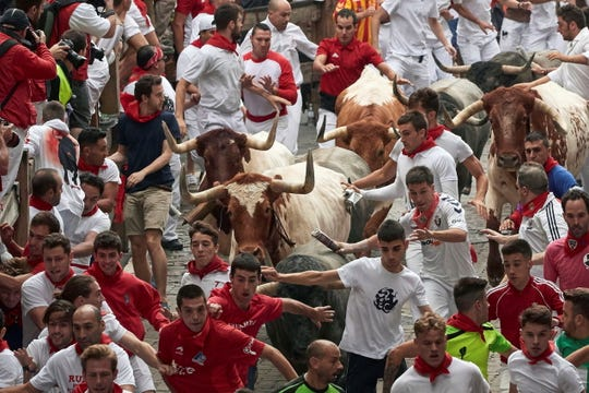 Several runners are chased by bulls during the San Fermin Festival on July 9.