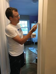 Virginia math teacher Bill Drake puts some finishing touches on painting his house.