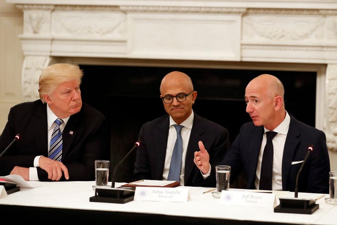 """In this June 19, 2017, file photo President Donald Trump, left, and Satya Nadella, Chief Executive Officer of Microsoft, center, listen as Jeff Bezos, Chief Executive Officer of Amazon, speaks during an American Technology Council roundtable in the State Dinning Room of the White House in Washington. Amazon and Microsoft are battling for a $10 billion opportunity to build the U.S. military its first """"war cloud."""""""