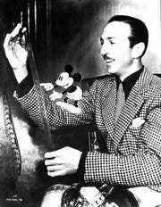 Walt Disney inspecting a filmstrip with an animated Mickey Mouse in the 'Mickey Mouse: From Walt to the World' exhibition.
