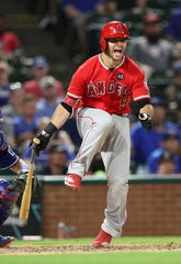 Angels second baseman Tommy La Stella reacts after fouling a ball off his leg and injuring himself against the Rangers.