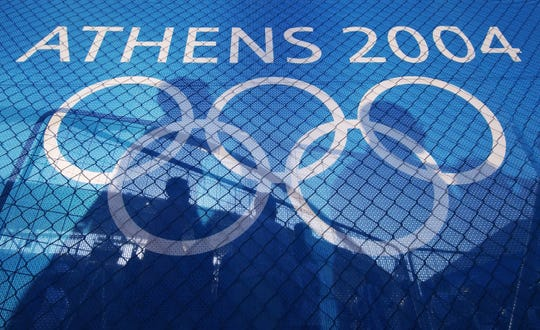 Shadows of spectators and the silhoutte of the Athens Olympic Stadium are cast on the banner bearing the Olympic rings during the opening ceremony of the 2004 Athens Olympic Games.
