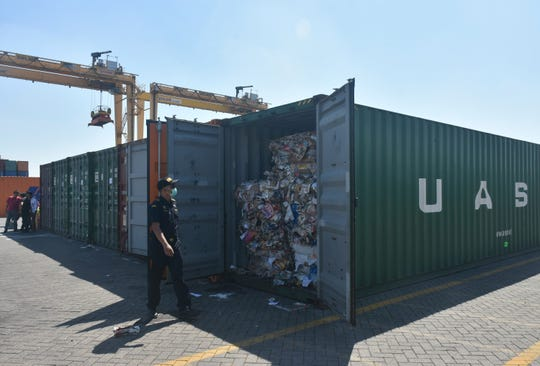 Indonesian custom officers open containers full of waste at the Tanjung Perak port in Surabaya, East Java, Indonesia, Tuesday, July 9, 2019.