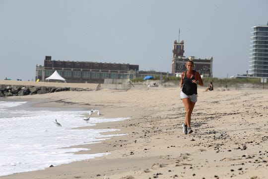 Heather Wanner of West Allenhurst runs along the beach during the morning hours in Loch Arbour, NJ Tuesday July 9, 2019.