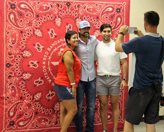 Abilene-based country singer Aaron Watson poses with two fans while a fan takes a cellphone souvenir before Watson's show Saturday in Big Lake.