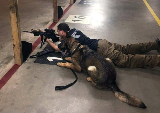 Staff Sgt. Nicholas Carmona takes aim at an indoor firing range as his military working dog Axa rests by his side in this undated photograph.