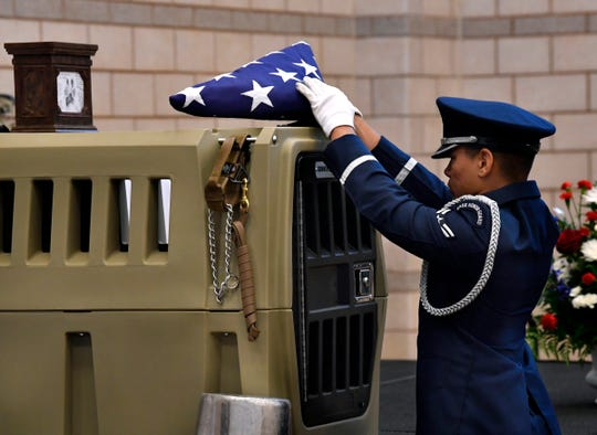Airman Justus Harris of the Dyess Honor Guard lays a folded flag upon the empty carrier of Axa, a military working dog at Dyess Air Force Base who died last month after an illness. Axa was attached to the 7th Security Forces and during her career assisted United States Border Patrol agents with identifying over 4,000 pounds of narcotics valued at nearly $10 million.