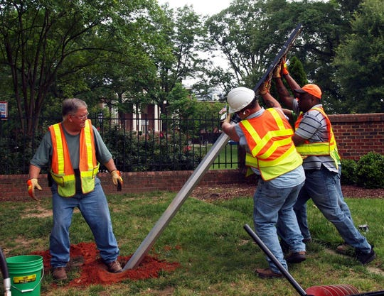 In this May 2016 photo, workers place the historic highway marker at St. Mary's School in Raleigh, N.C. The director of the North Carolina highway marker program says the sign was stolen in October 2017 and quickly dropped off in a park after some St. Mary's students learned of the theft on Snapchat.