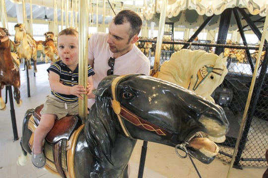 Luke Sowell, 1, of Johnson City rides the carousel for the first time, while getting a little support from his dad Justin, during the 7th annual Carousel Day on July 29, 2017 at CFJ Park in Johnson City.