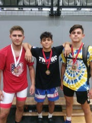 Johnson City's Dante Rigal is flanked by Chenango Valley's Colsten Volpe, left, and Chenango Forks' Logan Gumble after winning medals in last weekend's Ontario Cup.
