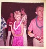 Then 31-year-old Pat Simanek sips on her cocktail at Mary Bubb's Apollo 17 launch party in a vibrant pink printed dress with a daffodil hairstyle.