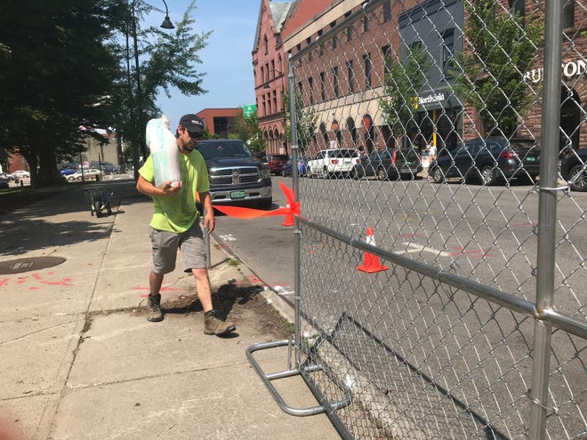 A crew from Middlebury Fence Co. haul sandbags to stabilize a chain-link fence they are erecting at Burlington's City Hall Park on Wednesday, July 10, 2019.  The park will remain closed to the public through late 2020 during a major rehabilitation project.