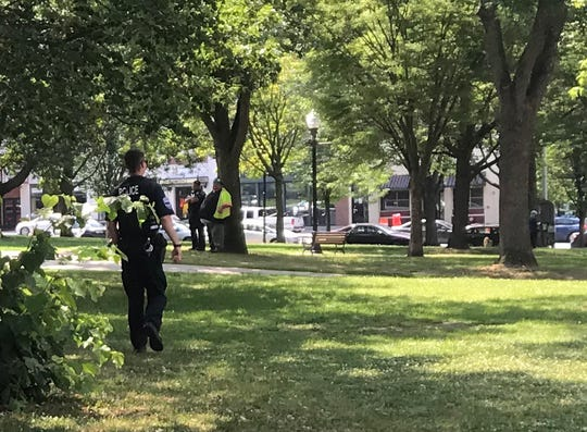 Police officers and construction workers gather in Burlington's City Hall Park during the erection of a perimeter fence on July 10, 2019. The park will remain closed until late 2020 during its rehabilitation.