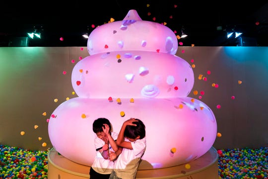 In this Tuesday, June 18, 2019, photo, two boys jokingly take cover as small toy poops gush from a giant poop-shaped inflatable at the Unko Museum in Yokohama, south of Tokyo. In a country known for its cult of cute, even poop is not an exception. A pop-up exhibition at the Unko Museum in the port city of Yokohama is all about unko, a Japanese word for poop. The poop installations there get their cutest makeovers. They come in the shape of soft cream, or cupcake toppings. (AP Photo/Jae C. Hong)
