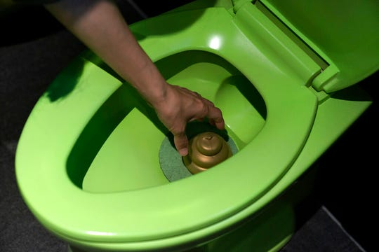 In this Tuesday, June 18, 2019, photo, a visitor reaches into a toilet bowl to pick up a toy poop at the Unko Museum in Yokohama, south of Tokyo. In a country known for its cult of cute, even poop is not an exception. A pop-up exhibition at the Unko Museum in the port city of Yokohama is all about unko, a Japanese word for poop. The poop installations there get their cutest makeovers. They come in the shape of soft cream, or cupcake toppings. (AP Photo/Jae C. Hong)