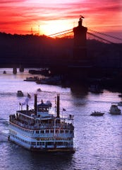 The Belle of Louisville heads up river Tuesday evening as the sun sets on the eve of the Tall Stacks celebration in downtown Cincinnati.