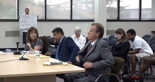 Christo Makropoulos, in the back, while Edison Mayor Tom Lankey's assistant, Mahesh Bhagia, center, testifies before the township committee of the whole investigating the origin of the 2017 racist campaign flyers.