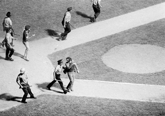 Chicago police move in to arrest some of the 7,000 fans who stormed the field during scheduled doubleheader between the White Sox and the Detroit Tigers, July 12, 1979. The second game was canceled after fans set bonfire in center field and threw disco records and firecrackers throughout the park during an Anti-Disco promotion by local radio station WLUP.