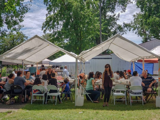 Guests gather and eat under tents at the the Midwest Buddhist Meditation Center's Sunday market in Warren on June 23, 2019.