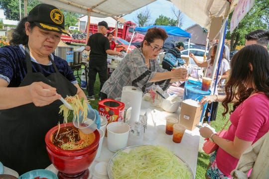 Thongphul Tansathian, left, prepares a green papaya salad while Lawan Chandruang serves Thai iced coffee at the Midwest Buddhist Meditation Center's Sunday market in Warren on July 7, 2019.