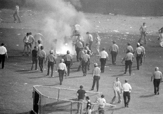 Chicago police disperse crowd in center field of Chicago's White Sox Park after hundreds of disco records were blown up between games of a double-header between the White Sox and the Detroit Tigers, July 12, 1980. Some 7,000 fans of a 50,000-fan crowd jammed the field during an Anti-Disco promotion sponsored by a local radio station. Second game had to be called when umpires ruled the field unfit for play.