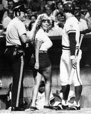 "Kansas City Royals' George Brett, right, watches as Kansas City policeman leads away Morganna Roberts also known as the ""Kissing Bandit"" after stealing a kiss from Brett as he came to bat in the first inning of game against the Baltimore Orioles, Aug. 22, 1977."
