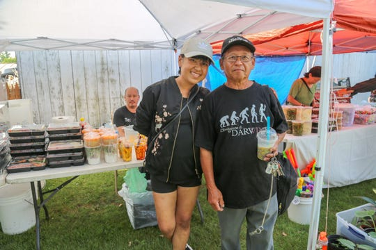 Kaying Chang, left, and her father, Dang Chang, are among the Hmong vendors at the Midwest Buddhist Meditation Center's Sunday market in Warren on July 7, 2019.