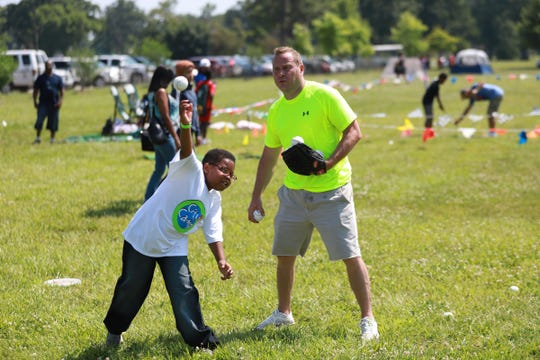Frank Pizzolato, 46, of Detroit, teaches a  young boy how to throw a baseball during the 2019 Metro Detroit Youth Day at Belle Isle Park in Detroit on Wednesday, July 10, 2019.