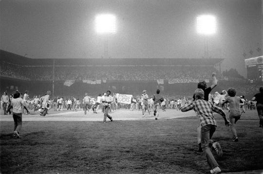 "Fans storm the field at Chicago's White Sox Park on Disco Demolition night in this July 12, 1979, file photo after the first game of a double header between the White Sox and Detroit Tigers. The promotion by a local radio station turned into a melee after hundreds of disco records were blown up on the field. The second game of the double header was called by umpires who declared the field unfit for play. A quarter-century later ""Disco Demolition Night"" remains the most infamous promotion in major league baseball history."