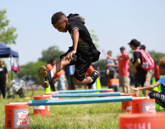 Christopher Johnson, 10, of Columbus, Ohio hurdles over obstacle during the 2019 Metro Detroit Youth Day at Belle Isle Park in Detroit on Wednesday, July 10, 2019.