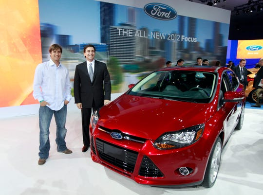"Mark Fields, Ford president for the Americas, right, and Olympic skier Johnny Moseley pose with the 2012 model year Ford Focus makes its debut at the LA Auto Show Wednesday, Nov. 17, 2010.  Moseley is scheduled to host a reality-type TV show titled ""Focus Reality America,"" centered around the car, next spring.  (AP Photo/Reed Saxon)"