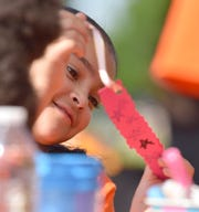 Valeria Wessels, 7, of Detroit, a member of the Belle Isle Nature Camp, smiles as she makes a book mark at the Detroit Institute of Arts tent.