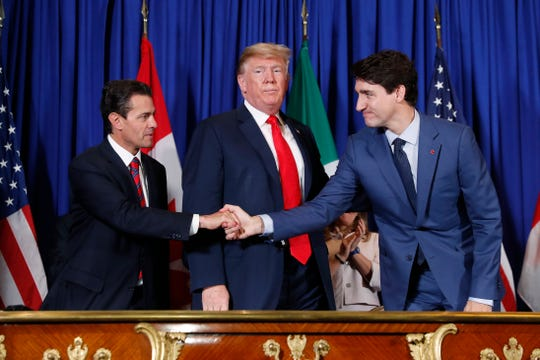 President Donald Trump, Canada's Prime Minister Justin Trudeau, right, and Mexico's President Enrique Pena Nieto, left, participate in the USMCA signing ceremony, Nov. 30, 2018, in Buenos Aires, Argentina.