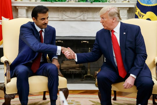 President Donald Trump shakes hands with Qatar's Emir Sheikh Tamim Bin Hamad Al-Thani in the Oval Office of the White House, Tuesday, July 9, 2019, in Washington.