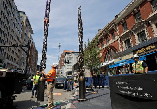 Workers use a crane to move bronze light pillars into place as a memorial to victims of the 2013 Boston Marathon bombings takes shape, Wednesday, July 10, 2019, at one of the bombing locations near the finish line on Boylston Street in Boston.