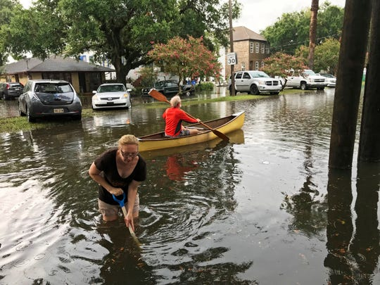 People cope with the aftermath of severe weather in the Broadmoor neighborhood in New Orleans, Wednesday, July 10, 2019.