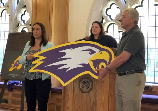 Elmira College Creative Director Kiersten Tarkett (left) and Elmira College President Charles Lindsay (right) show off a peelable version of the college's new logo as EC Athletic Director Renee Carlineo talks at the podium July 10, 2019 at Meier Hall on campus.