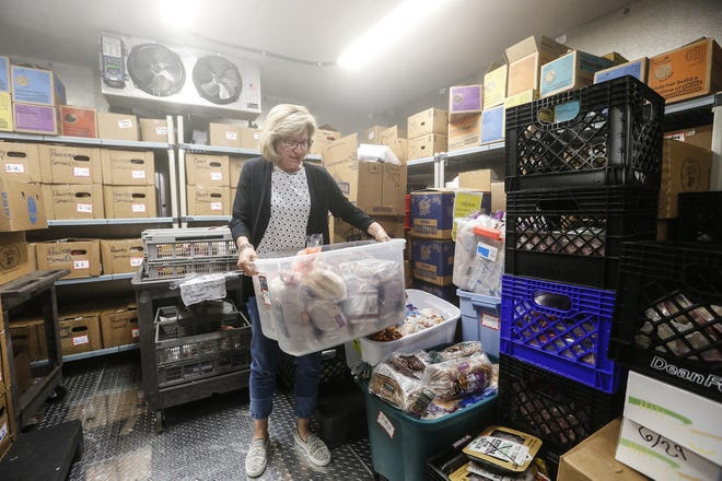 Sheri Wagner moves a tub of bread July 9, 2019, in the walk-in freezer at the Fondy Food Pantry.