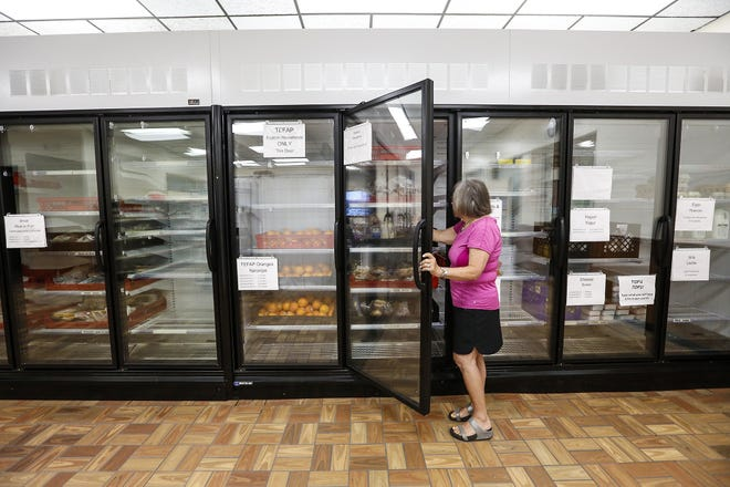 Food pantry volunteer Judy Cusick reaches into the new stand up cooler and freezer display July 9, 2019, at the Fondy Food Pantry in Fond du Lac, Wis.