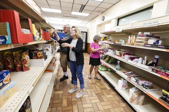 Food pantry volunteers Bob Kahl, Sheri Wagner and Judy Cusick make sure the shelves are ready for the pantry to open  July 9, 2019, at the Fondy Food Pantry in Fond du Lac, Wis.
