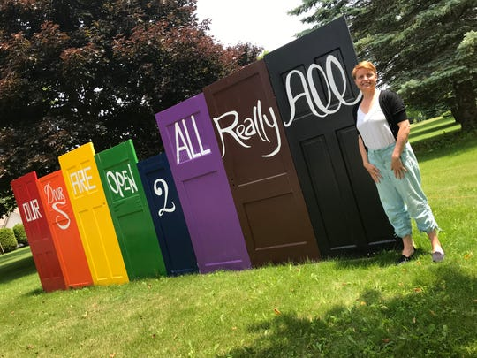 "Rev. Jennifer Emert, pastor for Algoma and West Kewaunee United Methodist churches, stands next to the welcoming sign that says ""Our Doors are Open 2 All Really All"" outside the Algoma church. Emert and the local churches are taking a stand against church rules they say discriminate against LGBTQ members and clergy persons."