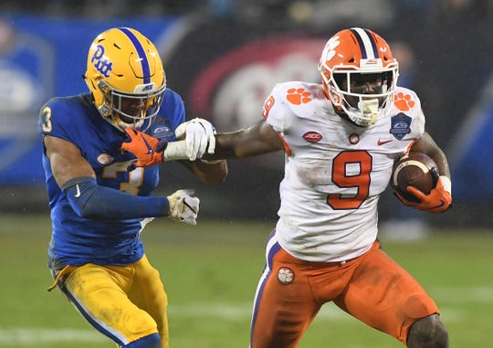 Clemson running back Travis Etienne (9) stiff arms Pittsburgh defensive back Damar Hamlin (3) during a long gain during the 2nd quarter of the Dr. Pepper ACC Championship at Bank of America Stadium in Charlotte, N.C. Saturday, December 1, 2017.
