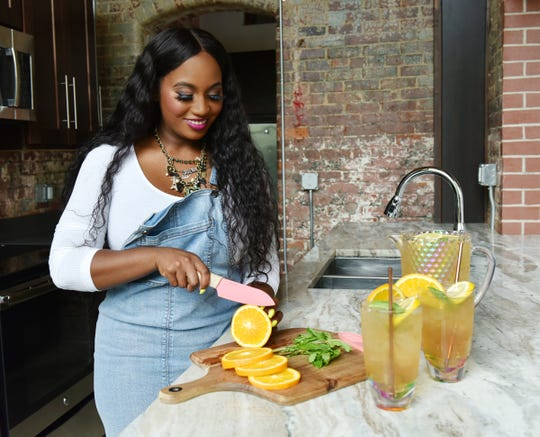 Adrienne Walker, owner of Chef A'Bella, slices oranges for her sweet tea.